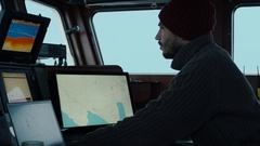 Captain of Commercial Fishing Ship Surrounded by Monitors and Screens Stock Footage