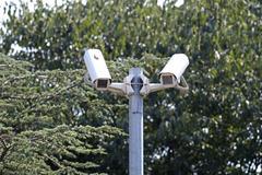 Security surveillance camera near green forest Stock Photos