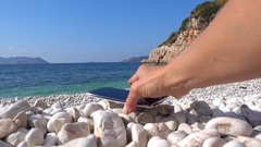 Placing a phone on pebbles on the beach 2 Stock Footage
