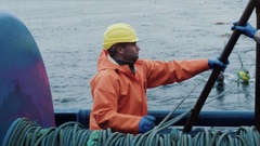 Fisherman Works on Commercial Fishing Ship that Pulls Trawl Net Stock Footage