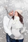 Happy couple expecting a baby in winter Stock Photos