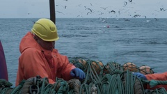 Crew of Fishermen Work on Commercial Fishing Ship that Pulls Trawl Net Stock Footage