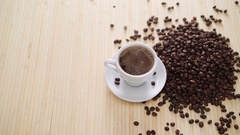 A white cup of evaporating coffee on the table with roasted beans in 4K Stock Footage