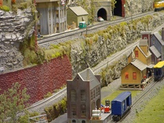 Model train cars zooming in a small toy town Stock Footage