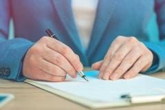 Close up of female hands writing signature on business agreement Stock Photos