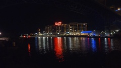 CLEVELAND, FLATS AREA, VIEW ACROSS CUYAHOGA RIVER, CREW TEAM ROWS BY, NIGHT SHOT Stock Footage