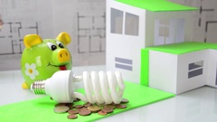 Woman  places the saving light bulb in front of the model of house and coins. Stock Footage