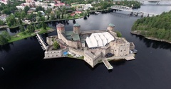 Flying away from Olavinlinna Castle with the city of Savonlinna as backdrop Stock Footage