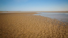 Time lapse of ocean tidal water flooding a sand bank Stock Footage