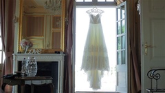 Lace wedding dress hang in doorway light waiting for bride morning tracking pan Stock Footage