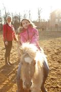 Young girl riding pony, mother watching from behind Stock Photos