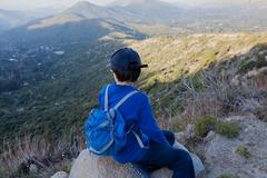 Boy sitting on boulder looking out over Andes, Valparaiso, Chile Stock Photos