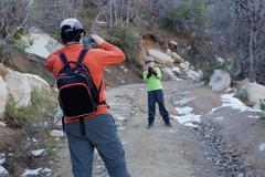 Man photographing son holding snowball in Andes, Valparaiso, Chile Stock Photos
