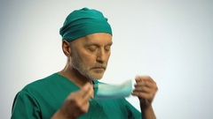 Male doctor putting on face mask to examine patient, protection against disease Stock Footage