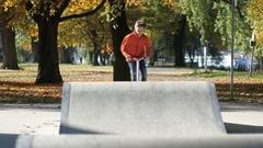 Teenage Boy jumping on Skateboard Ramp in Autumn Stock Footage