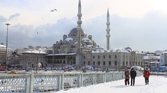 Yeni Mosque under snow. People walk through snow a day after city was hit by sto Stock Footage