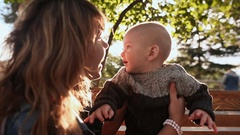 Happy young mother playing with the baby for a walk. They gets ray of sunshine Stock Footage