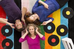 People lying on carpet and listening to music Stock Photos