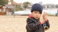 A boy talking on the smartphone, putting an incoming call on hold and continuing Stock Footage