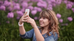 A young girl takes pictures on your phone, selfi among the flowers Stock Footage