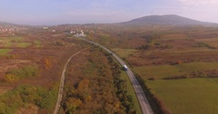 Cars and trucks traffic On Country Road. Aerial motorway through autumn nature Stock Footage