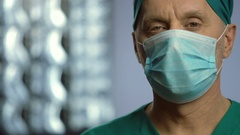 Experienced spine surgeon, serious man wearing face mask looking into camera Stock Footage