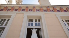 Wedding dress hangs in doorway at balcony waits for bride vertical pan light  Stock Footage