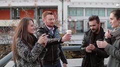 Four beautiful young people joyfully clink cardboard cups standing near a bridge Stock Footage