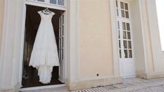 Wedding dress hangs in doorway at balcony waits for bride horizontal pan light Stock Footage