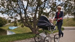 Young happy grandmother walks with my little grandson, sitting in a wheelchair Stock Footage