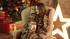 Girl sitting near a Christmas tree with a blanket and drinks tea Stock Footage