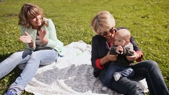 Happy mother, grandmother and little baby resting on green grass Stock Footage