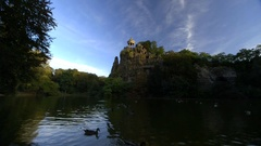 Dozens of Ducks and pagoda on lake at Parc des Buttes-Chaumont Stock Footage