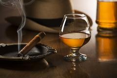 Alcoholic drinks and cigar on wooden table Stock Photos