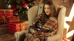 A girl sits in a big chair near a Christmas tree and keeps the phone Stock Footage