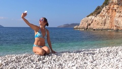 Woman selfie addict poses on the beach Stock Footage