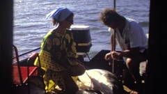 1969: woman wearing caftan on boat with man and fish and man joins another at Stock Footage