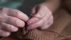 Young woman knitting a scarf with maroon yarn. Stock Footage