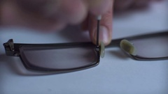 Hands holding a screwdriver tightening a loosened nut on a pair of spectacles. Stock Footage