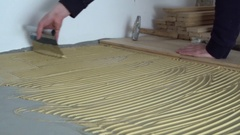 Worker applied adhesive for parquet. Home renovation Stock Footage