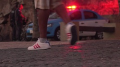 Police car in background with flashing lights and people walking on sidewalk Stock Footage