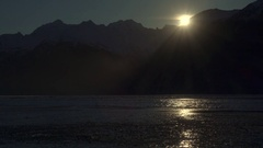 Disappearing Sun Behind Cold and Icy Mountain Scene Stock Footage