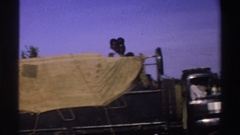 1969: a truck with a tarp partially covering the cargo bed transports black men Stock Footage