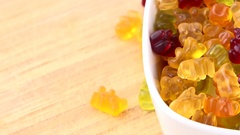 Gummy Bears (rotating on a wooden plate; seamless loopable; 4K) Stock Footage