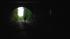 Girl walking down dark tunnel Stock Footage