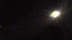 Man walking down dark tunnel towards light Stock Footage