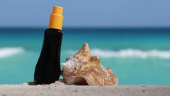 Sunscreen protection cream and seashell on white sand at beach Stock Footage