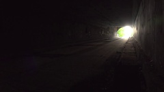 Man walks away from camera through dark tunnel with hands spanned open Stock Footage