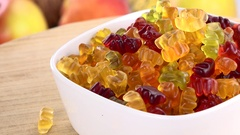 Gummy Bears rotating on a wooden plate (not loopable; 4K) Stock Footage