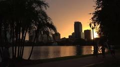 People enjoy Orlando skyline at sunset, Lake Eola Park, Florida, USA Stock Footage